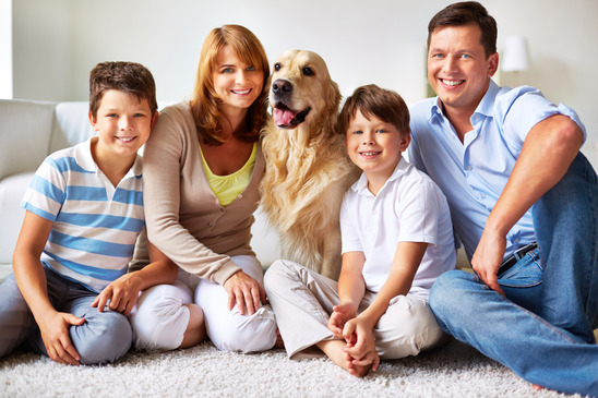 Portrait of happy father, mother and kids with fluffy Labrador looking at camera